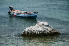 Fishing boat anchored in sea water stock photo