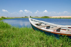 Fishing boat anchored in lagoon with green grass and dunes. And clouds in background near Lobito, Angola Royalty Free Stock Photo