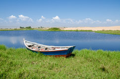 Fishing boat anchored in lagoon with green grass and dunes. And clouds in background near Lobito, Angola Royalty Free Stock Photos