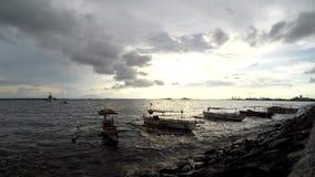 Fishing boat anchored on sea shore at twilight dusk sunset. silhouettes. Bay walk, Manila, Philippines - July 9, 2017: Fishing boats anchored on sea shore at stock video