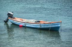 Fishing boat anchored in sea water stock images