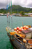 Fishing boat Avatiu harbor in Rarotonga, Cook Islands. Deep sea fishing boat with orange mooring bouys and fishing poles stands ready in the Avatiu harbor in Royalty Free Stock Photography