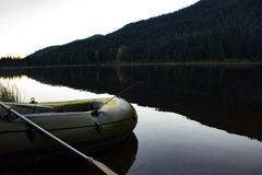 Fishing boat awaiting takeoff. Inflatable fishing boat on the shore with paddles and fishing gear at Trillium Lake, Oregon Stock Photo