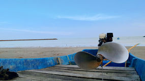 Fishing boat back from sea on sandy beach on sunny day Stock Images