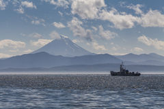 Fishing boat on the background of the volcano. Royalty Free Stock Photos
