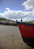 Fishing boat on the beach. Bright red fishing boat moored on the beach Stock Image