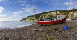 Fishing Boat on the Beach at Beer in Devon. Red fishing Boat on the beach at Beer on the Jurassic Coast in Devon Royalty Free Stock Image