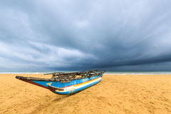 Fishing boat on the beach with dark clouds above the ocean Royalty Free Stock Photo