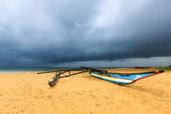 Fishing boat on the beach with dark clouds above the ocean Royalty Free Stock Image