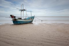 A fishing boat on a beach by the sea royalty free stock photos