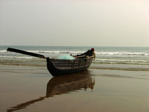 Fishing boat on the beach. Small fishing boat on the wet sands at Mandarmoni, West Bengal, India Royalty Free Stock Image