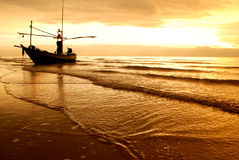 Fishing boat on the beach. In sunrise time stock photos