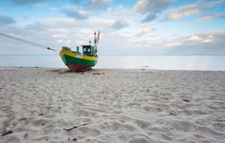 Fishing boat on the beach. Tranquil evening landscape. Royalty Free Stock Photo
