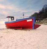 Fishing boat on the beach. Tranquil evening landscape. Royalty Free Stock Image