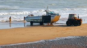 Fishing boat being pulled by tractor. stock photography
