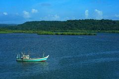 Fishing boat on blue river Royalty Free Stock Photos