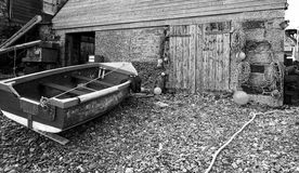 Fishing Boat and Boat Shed - Fishing Industry. Boat with fisherman's jacket on near boat shed on shingle beach - black and white royalty free stock photos