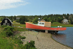 Fishing Boat. Bright red fishing boat at the shore in eastern Nova Scotia royalty free stock images