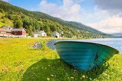 Fishing boat beside calm lake/river water. Old wooden fishing boat. Wooden fishing boat near lake water and small town. On background Royalty Free Stock Photos