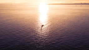 Fishing boat on the calm sea wave. Bird view of a small fishing boat on the calm sea wave, shot sunset time royalty free stock photos