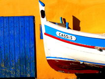 Fishing Boat at Cassis, France. A mixed hue of colors with a tiny fishing boat against a sea wall stock photography