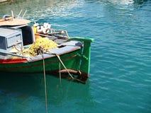 Fishing boat in clear water. Small fishing boat - port Agios Nikolaos, Crete Stock Image