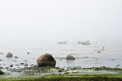 Fishing boat at coast foggy in the morning Stock Photos