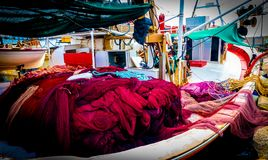 Fishing boat with colorful nets at the dock stock images