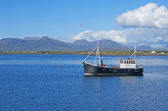 Fishing Boat in Connemara. A fishing boat at Roundstone, Galway in Ireland with the Connemara Mountains (called variously the Twelve Pins or Twelve Bens) in the Royalty Free Stock Photos