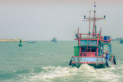 Fishing boat is cruising out to the open sea in the morning. Stock Photo