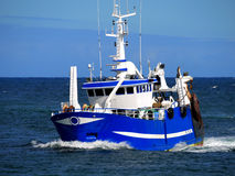 Fishing Boat D. Fishing boat underway at speed over blue sky and sea Stock Image