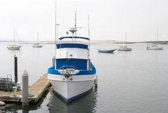 Fishing Boat At Dock. A powerful small size fishing boat tied to the marina dock stock image