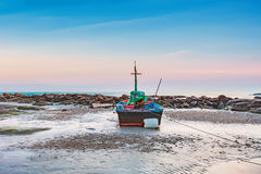 Fishing boat dock on the beach with sunset sky Stock Images