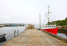 Fishing boat at dock. A red fishing boat or vessel in a harbour with fog rolling in royalty free stock photo