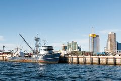 Fishing Boat Docked at the Embarcadero in San Diego. A fishing boat docked at a pier along the Embarcadero in the San Diego, California Harbor, with the downtown royalty free stock image
