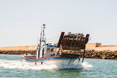 Fishing boat and dredge at sea. Stock Photos