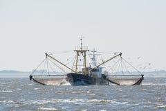 Fishing boat on Dutch wadden sea. Fishing boat with nets on Dutch wadden sea stock photography