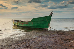Fishing boat early in the morning on sandy beach of the Baltic Sea, Latvia, Europe Royalty Free Stock Images