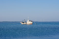 Fishing boat in the estuary in the background of wind turbines Stock Image