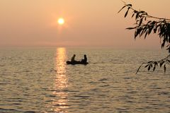 Fishing in the boat on the evening lake stock photo