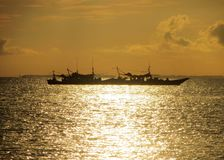 Fishing Boat. Fishing expedition under the golden rays of the rising sun royalty free stock photography
