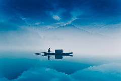 Fishing-boat in fairyland. Fishing-boat on the Dongjiang Lake surrounded by mist flowing along the mountains and on the surface. The lake is located in Zixing royalty free stock photography
