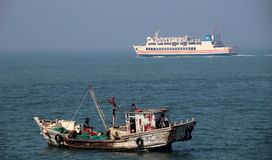 A fishing boat and the ferry Stock Images