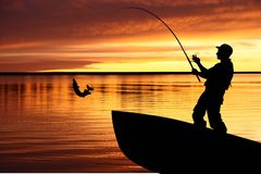 Fishing boat and fisherman with catching pike. Fish at sunrise background Royalty Free Stock Photo