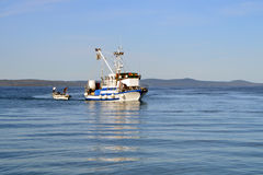 Fishing boat with fishermen in calm blue sea Stock Image