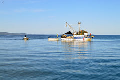 Fishing boat with fishermen in calm blue sea Stock Photo