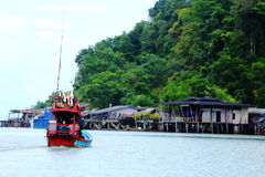 Fishing boat float to village port and mountain which is way to Stock Photography