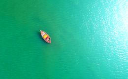Fishing boat floating in the sea. The beautiful bright blue wate. R in a clear day.Aerial view.Top view Stock Images