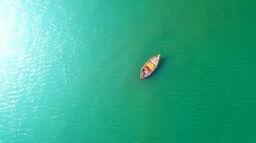 Fishing boat floating in the sea. The beautiful bright blue wate. R in a clear day.Aerial view.Top view Stock Image