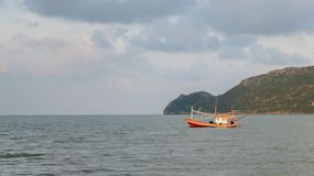Fishing boat floating in the sea. A fishing boat anchored in the sea near the shore on a cloudy day with island at the background , Sam Roi Yot, Prachuap Khiri Royalty Free Stock Photography
